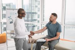 Nice positive men shaking hands. Patient and doctor. Nice positive men looking at each other while shaking hands stock image