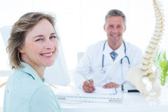 Patient and doctor smiling at camera. In medical office Royalty Free Stock Photography