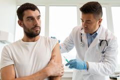 Patient and doctor with syringe doing vaccination Royalty Free Stock Images
