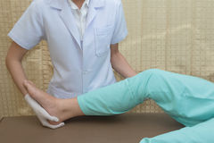 Patient doing knee exercises with physical therapist Stock Photo
