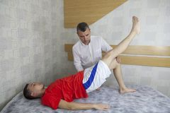 Patient doing some special exercises under supervision of physic stock photography