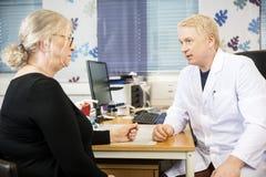 Patient Doktor-Communicating With Senior am Schreibtisch lizenzfreies stockfoto