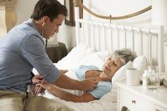 Patient Doktor-Examining Senior Female im Bett zu Hause Stockfotos