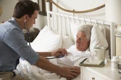 Patient Doktor-Examining Senior Male im Bett zu Hause Stockbilder