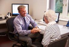 Patient Doktor-Greeting Senior Female mit Händedruck Lizenzfreies Stockfoto