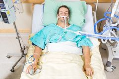 Patient With Endotracheal Tube Resting In Hospital. High angle view of critical patient with endotracheal tube resting on bed in hospital stock images