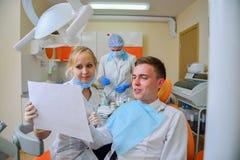 Patient et dentiste dans la clinique regardant l'instantané Images libres de droits