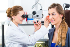 Patient in a examination by doctor in clinic. Doctor - Young female doctor or ENT specialist - with a patient in her practice, examining the ear with a endoscope Stock Photography