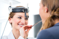 Patient in a examination by doctor in clinic. Doctor - Young female doctor or ENT specialist - with a patient in her practice, examining the throat with a Royalty Free Stock Photography