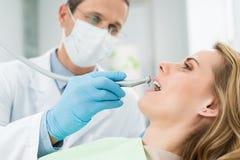 Patient féminin à la procédure dentaire à l'aide de la perceuse dentaire dedans moderne photographie stock