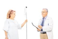 Patient féminin dans la robe d'hôpital appelant l'infusion et son docteur Image libre de droits