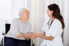 Patient féminin de docteur Consoling Handicapped Senior photographie stock