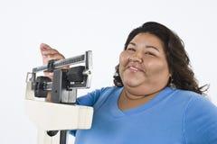 Patient féminin employant l'échelle de poids à la clinique Images libres de droits
