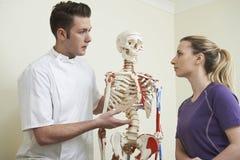 Patient féminin en consultation avec l'ostéopathe Photographie stock libre de droits