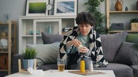 Patient féminin prenant la température avec la médecine potable de thermomètre à la maison banque de vidéos