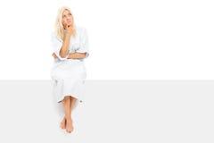 Patient féminin songeur s'asseyant sur un panneau vide Image libre de droits