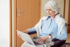 Patient féminin supérieur à l'aide de l'ordinateur images stock