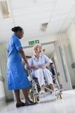 Patient féminin supérieur dans le fauteuil roulant et l'infirmière dans l'hôpital Image stock