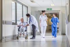 Patient féminin supérieur dans le fauteuil roulant et le docteur dans l'hôpital Images stock