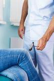 Patient för knä för doktorsprostukivethammare kvinnlig i hans kontorsmedetsinkom Doktorn undersöker patient&en x27; s-knä Arkivbild