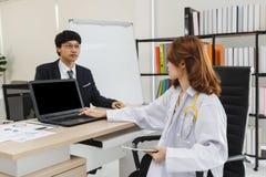 Patient f?r ung asiatisk kvinnlig doktor f?r medicin konsulterande i sjukhuskontor H?lsov?rd- och l?karunders?kningbegrepp fotografering för bildbyråer