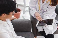 Patient f?r ung asiatisk kvinnlig doktor f?r medicin konsulterande i sjukhuskontor H?lsov?rd- och l?karunders?kningbegrepp arkivbild