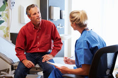 Patient And Female Doctor Have Consultation In Hospital Room stock photography