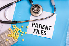 Patient files words written on medical blue folder. With patient files, pills and stethoscope on background stock photo