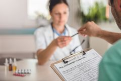 Patient filing health insurance claim form stock photos