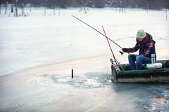 Patient fisherman pulls hooked fish from water stock photo