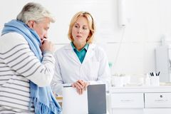 Patient with flu. Doctor talking to mature sick coughing patient with influenza in clinics Stock Images