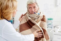 Patient with flu. Sick mature men with thermoteter in his mouth listening to doctor advice in clinics Royalty Free Stock Photography