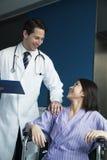 Patient féminin de sourire de jeunes s'asseyant dans un fauteuil roulant, regardant le docteur se tenant près de elle Photo libre de droits