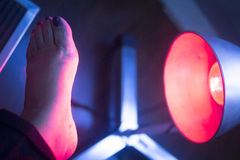 Patient foot in red physiotherapy heat treatment Stock Image