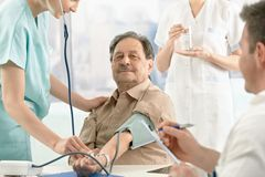 Patient getting blood pressure measurement. Nurse and doctor examining Royalty Free Stock Image