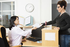 Patient Giving Reports To Doctor In Office Stock Photo