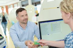 Patient giving social security card to hospital employee royalty free stock photo