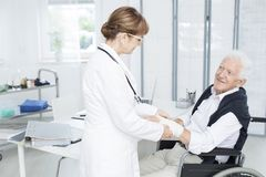 Patient grateful for fixing hand. Smiling elderly patient grateful for help of a doctor in white uniform fixing his hand Stock Photos