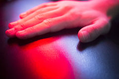 Patient hand in red physiotherapy heat treatment. Under hot light royalty free stock image