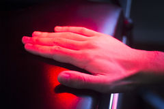 Patient hand in red physiotherapy heat treatment Stock Image