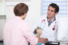 Patient handing card to doctor Royalty Free Stock Photography