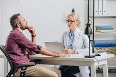 patient having appointment with female physiotherapist in eyeglasses