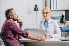 patient having appointment with smiling physiotherapist