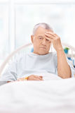 Patient having a headache and lying in hospital bed Royalty Free Stock Photos