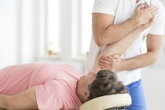 Patient having her hand stretched. Senior patient is having her right hand stretched in a pnf exercise by a physiotherapist Royalty Free Stock Images