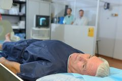 Patient having xray medical staff shielded behind partition. Radiology Stock Image