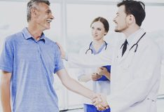 Patient and his Confident Doctor Shake Hands. stock photo