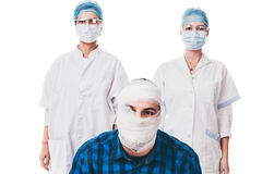 Patient and his doctors. Two women with hygienic masks and protection glasses looking at their bandaged patient - isolated on white royalty free stock images