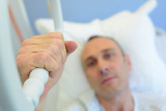 Patient holding hand on hospital bed to recover. Patient holding his hand on a hospital bed to recover Stock Images