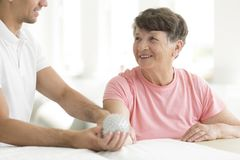 Patient holding spiked rehabilitation ball. Hospital patient holding a grey, spiked rehabilitation ball in her right hand during physiotherapy Royalty Free Stock Image